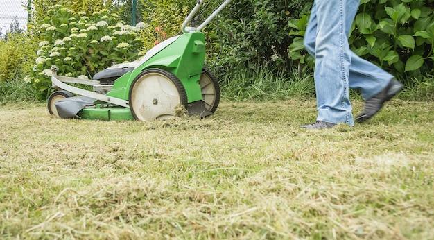 Homme supérieur tondant la pelouse avec une tondeuse à gazon