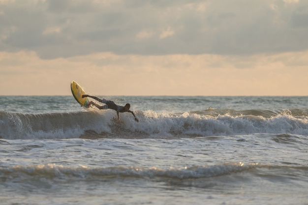 Un homme avec un surf dans ses mains au bord de la mer