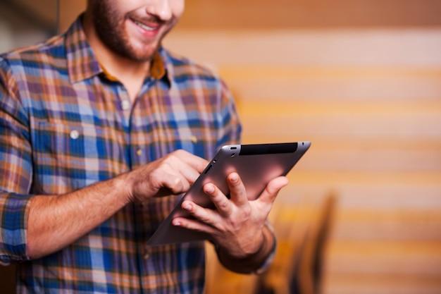 Homme surfant sur le net. beau jeune homme travaillant sur tablette numérique et souriant en se tenant debout à l'intérieur