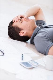 Homme surmené. vue de dessus d'un jeune homme déprimé tenant la main sur le front en position couchée sur le sol avec des documents et une tasse de café dessus