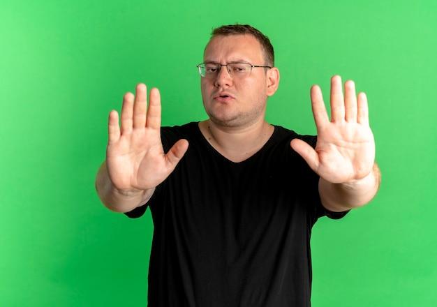 Homme en surpoids dans des verres portant un t-shirt noir faisant arrêter de chanter à mains ouvertes debout sur un mur vert