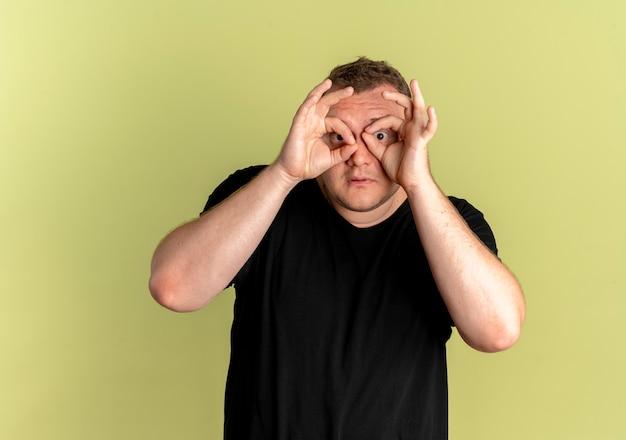 Homme en surpoids dans des verres portant un t-shirt noir faisant un geste binoculaire avec les doigts à travers les doigts debout sur un mur léger