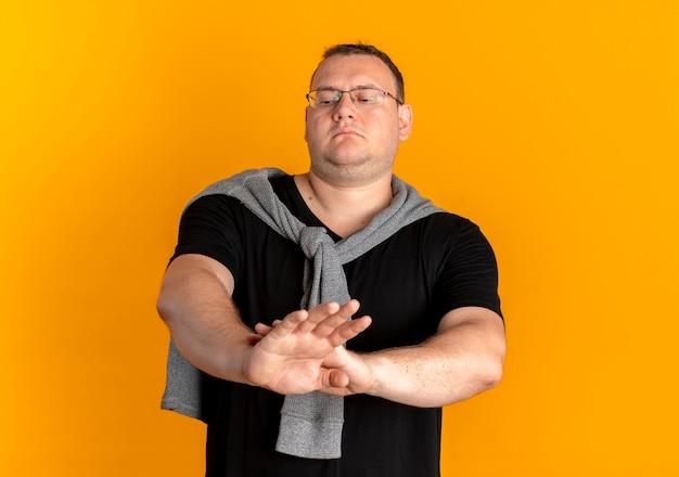 Homme en surpoids dans des verres portant un t-shirt noir faisant panneau d'arrêt avec un visage sérieux debout sur un mur orange