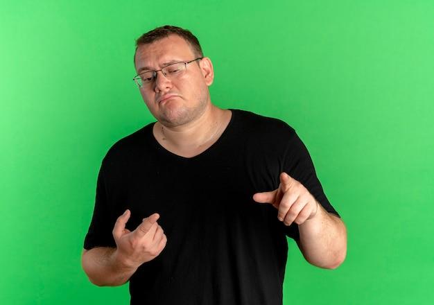 Homme en surpoids dans des verres portant un t-shirt noir pointant avec l'index debout sur le mur vert