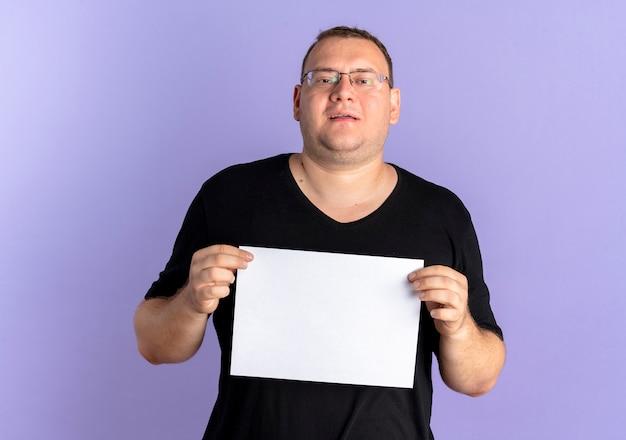 Homme en surpoids dans des verres portant un t-shirt noir tenant une feuille de papier vierge avec sourire debout sur un mur bleu