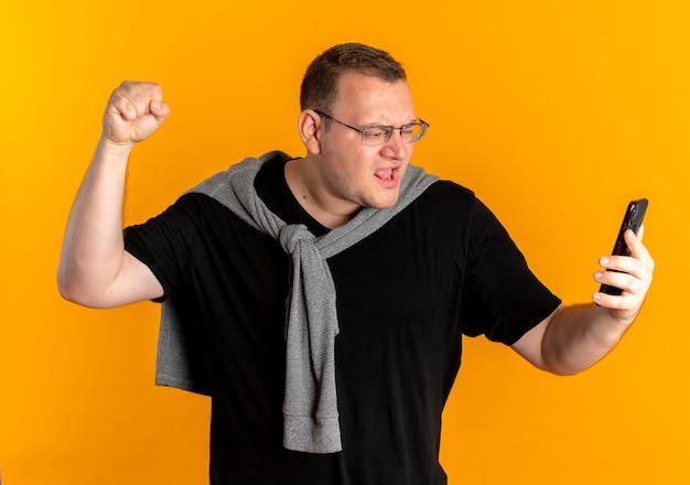 Homme en surpoids dans des verres portant un t-shirt noir tenant le poing de clanching smartphone se réjouissant de son succès sur orange