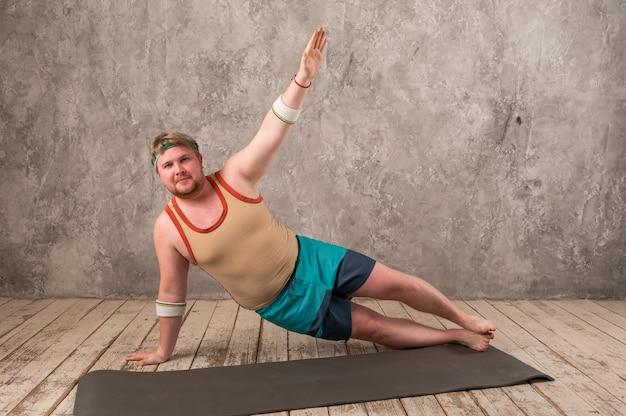 Homme en surpoids exercice, faire des exercices d'étirement sur un tapis de yoga, regarder des vidéos de remise en forme en ligne sur un ordinateur portable à la maison.
