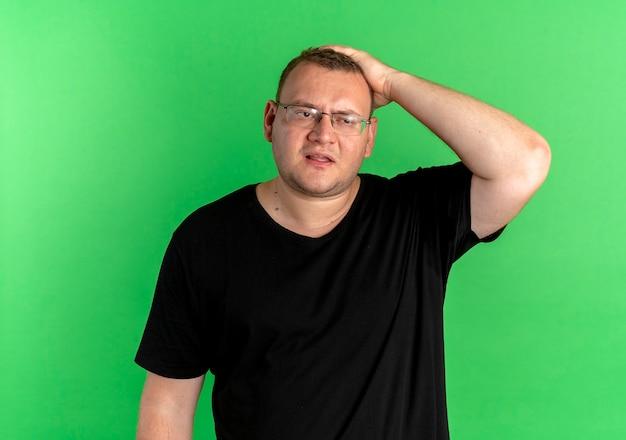 Homme en surpoids à lunettes portant un t-shirt noir à la confusion avec la main sur sa tête pour erreur oublié quelque chose d'important sur le vert