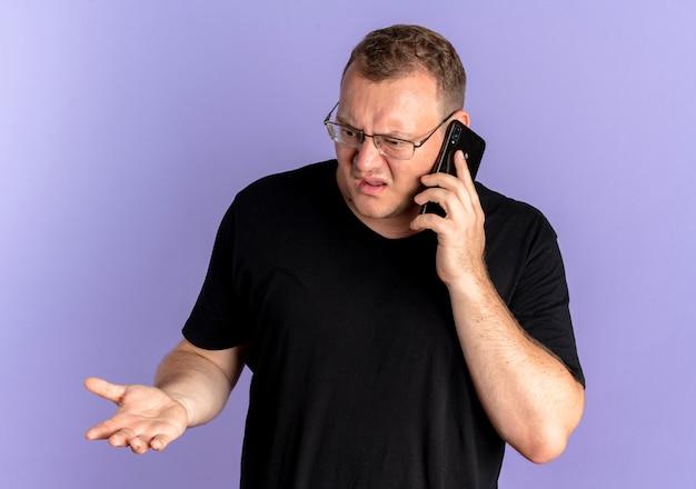 Homme en surpoids à lunettes portant un t-shirt noir à la confusion et mécontent tout en parlant au téléphone mobile sur bleu
