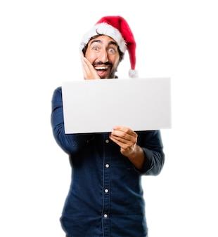 Homme surpris avec une affiche et le chapeau de santa