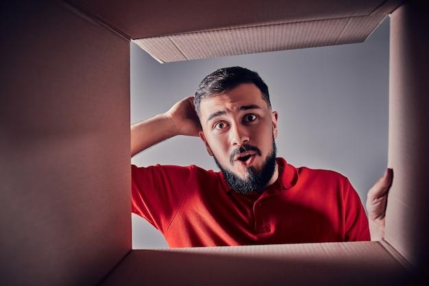 L'homme surpris déballant, ouvrant la boîte en carton et regardant à l'intérieur. le paquet, la livraison, la surprise, le concept de mode de vie cadeau. concepts d'émotions humaines et d'expressions faciales