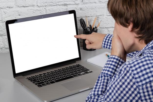 Homme surpris montrant à l'écran d'un ordinateur portable avec son doigt. maquette avec espace de copie