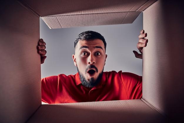L'homme surpris ouvrant la boîte en carton et regardant à l'intérieur. le paquet, la livraison, la surprise, le cadeau, le concept de style de vie. concepts d'émotions humaines et d'expressions faciales