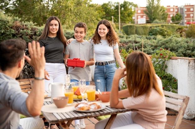 Homme surpris par un cadeau lors d'une réunion de famille