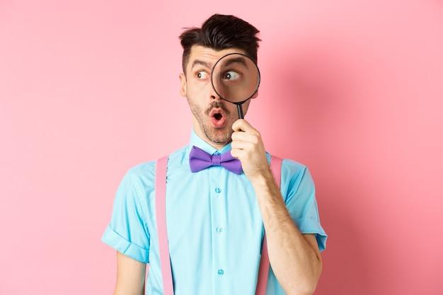 Homme surpris qui dit wow et regarde de côté à travers une loupe, vérifie l'offre promotionnelle, debout sur le rose.