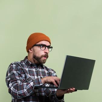 Homme surpris en regardant un ordinateur portable