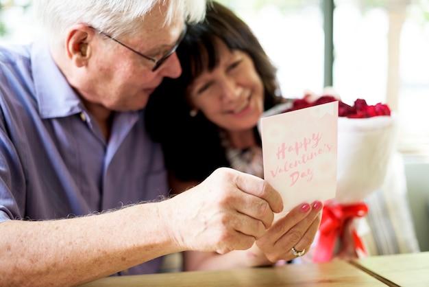 L'homme a surpris sa femme avec une carte et un bouquet de fleurs