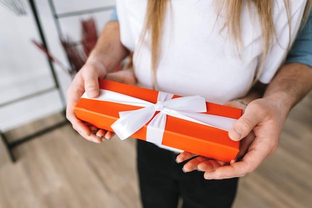 L'homme a surpris sa petite amie avec un cadeau, un couple heureux célébrant la saint-valentin ou un anniversaire