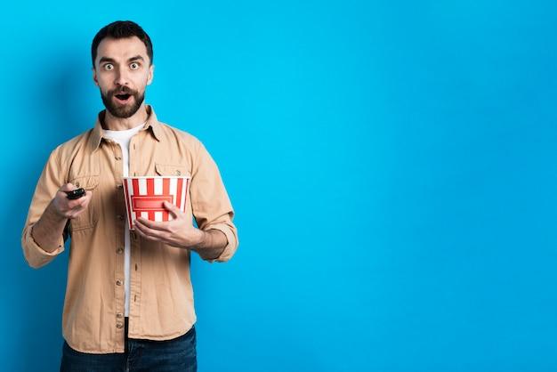 Homme surpris avec seau à pop-corn et télécommande