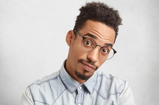 Homme surpris sérieux avec visage ovale, apparence spécifique, regarde à travers de grandes lunettes,