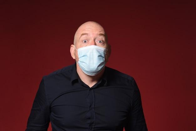 Homme avec surprise d'expression de masque médical sur fond rouge