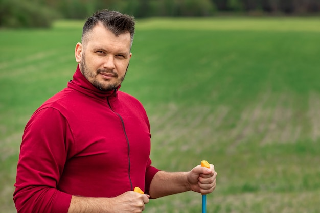 Un homme en survêtement est engagé dans la marche nordique