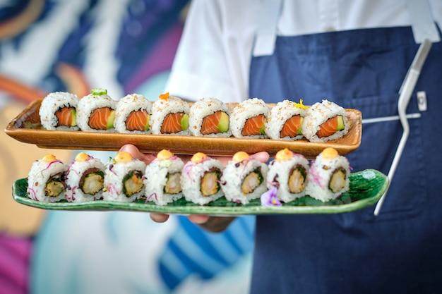 Homme de sushi tenant des assiettes de sushis fraîchement préparés