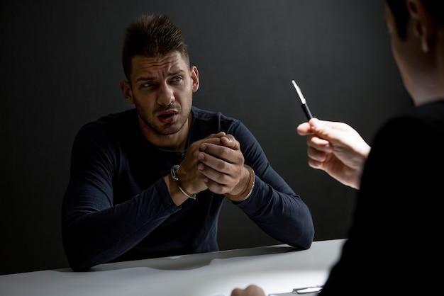 Homme suspect ou criminel avec des menottes dans la salle d'interrogatoire