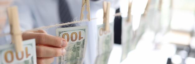 Homme suspendu des billets d'un dollar américain sur une corde en gros plan