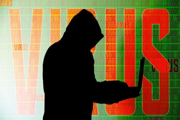 L'homme en sweat à capuche pirate des données personnelles sur fond vert. sécurité des informations. concept de virus virtuel. protection des informations. mauvais mot de passe.