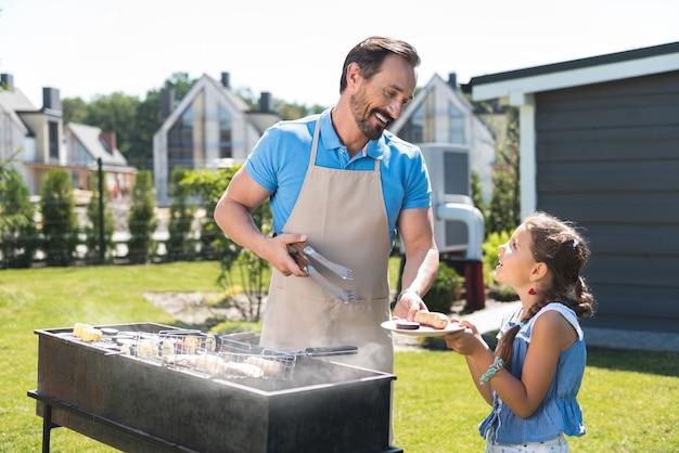 Homme sympathique agréable tenant une assiette avec de la nourriture tout en le donnant à sa fille