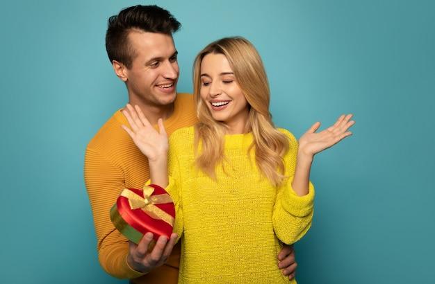 Un homme sympathique aux cheveux noirs corbeau couvre les yeux de sa petite amie, la regarde avec un grand sourire et tient une boîte rouge en forme de cœur dans sa main droite.