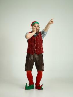 Homme sympathique habillé comme un drôle de gnome posant sur un gris isolé