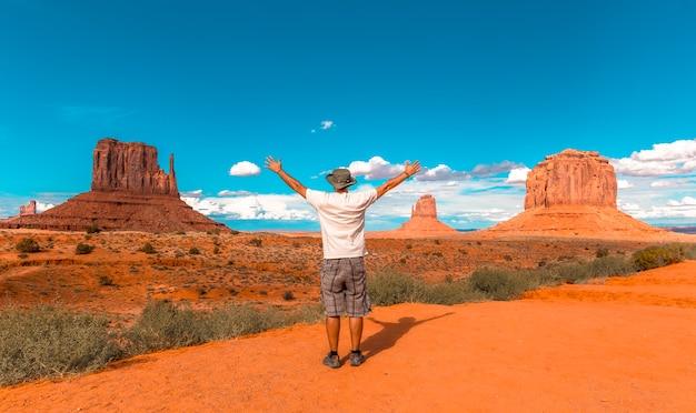 Homme en t-shirt blanc et chapeau vert avec les bras levés dans le parc national de monument valley à the mittens