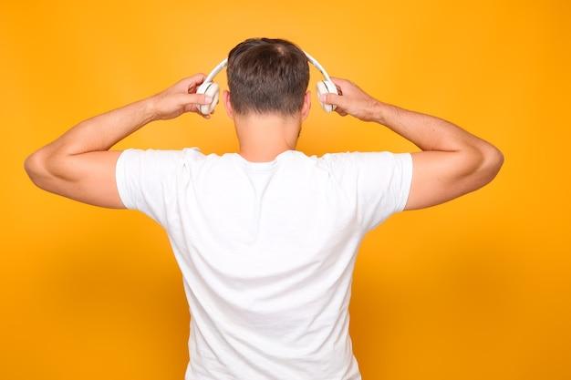 Un homme en t-shirt blanc avec des écouteurs blancs sur la tête se tient le dos.