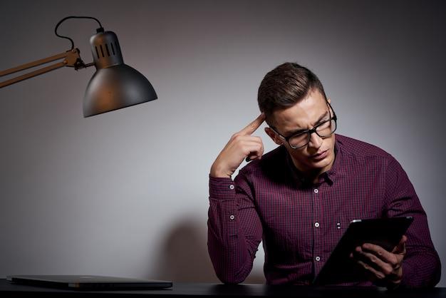 Un homme en t-shirt blanc avec un ordinateur portable et une tablette électronique travaille à la table
