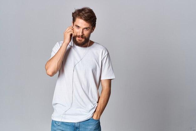 Homme en t-shirt blanc portant un casque de divertissement musical