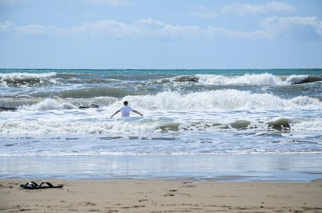 L'homme en t-shirt blanc avec ses bras écartés entre dans la mer dans une forte tempête.