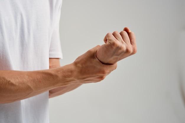 Un homme en t-shirt blanc tenant une main douloureuse au poignet