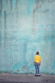 Homme en t-shirt jaune, levant les yeux sur un mur
