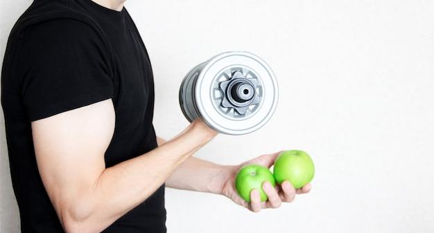Un homme en t-shirt noir se tient de profil et tient des haltères et des pommes vertes