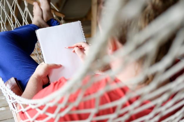 Homme en t-shirt rouge et pantalon bleu se trouve dans un hamac et dessine dans un carnet de croquis