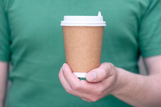 Un homme en t-shirt vert tenant une tasse en papier marron avec du café ou du thé en gros plan