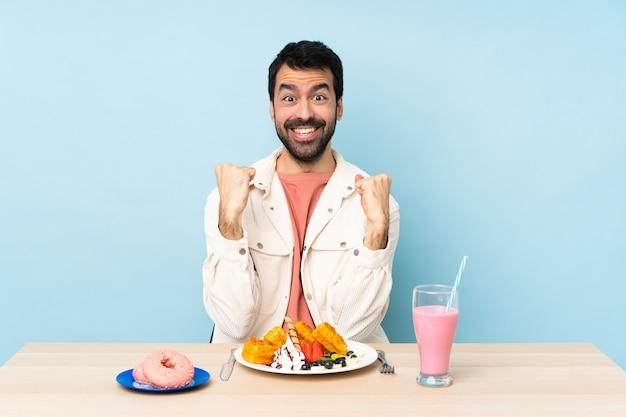 Homme, table, avoir, petit déjeuner, gaufres, milkshake, célébrer, victoire, gagnant, position