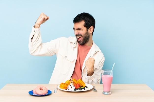 Homme, table, avoir, petit déjeuner, gaufres, milkshake, célébrer, victoire