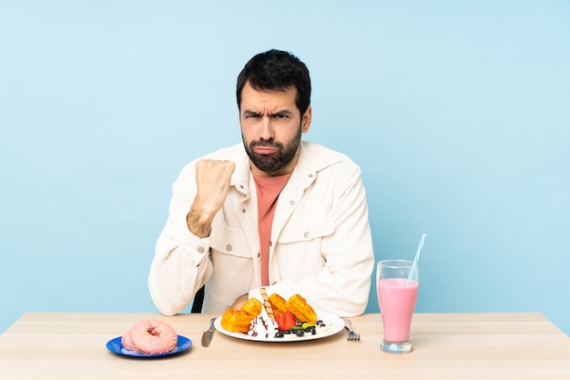 Homme, table, avoir, petit déjeuner, gaufres, milkshake, colère, geste