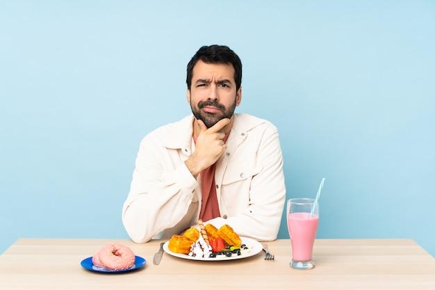 Homme, table, avoir, petit déjeuner, gaufres, milkshake, pensée