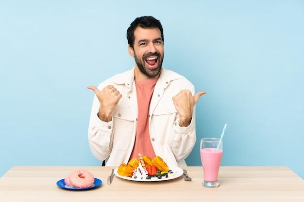 Homme, table, avoir, petit déjeuner, gaufres, milkshake, pouces, haut, geste, sourire