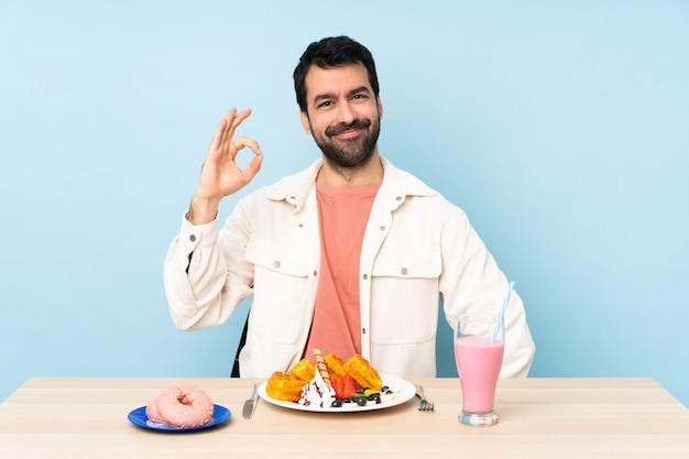 Homme, table, avoir, petit déjeuner, gaufres, milkshake, projection, ok, signe, doigts