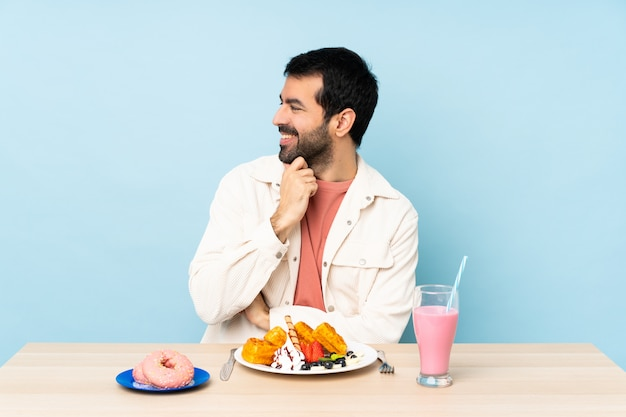 Homme, table, avoir, petit déjeuner, gaufres, milkshake, regarder, côté